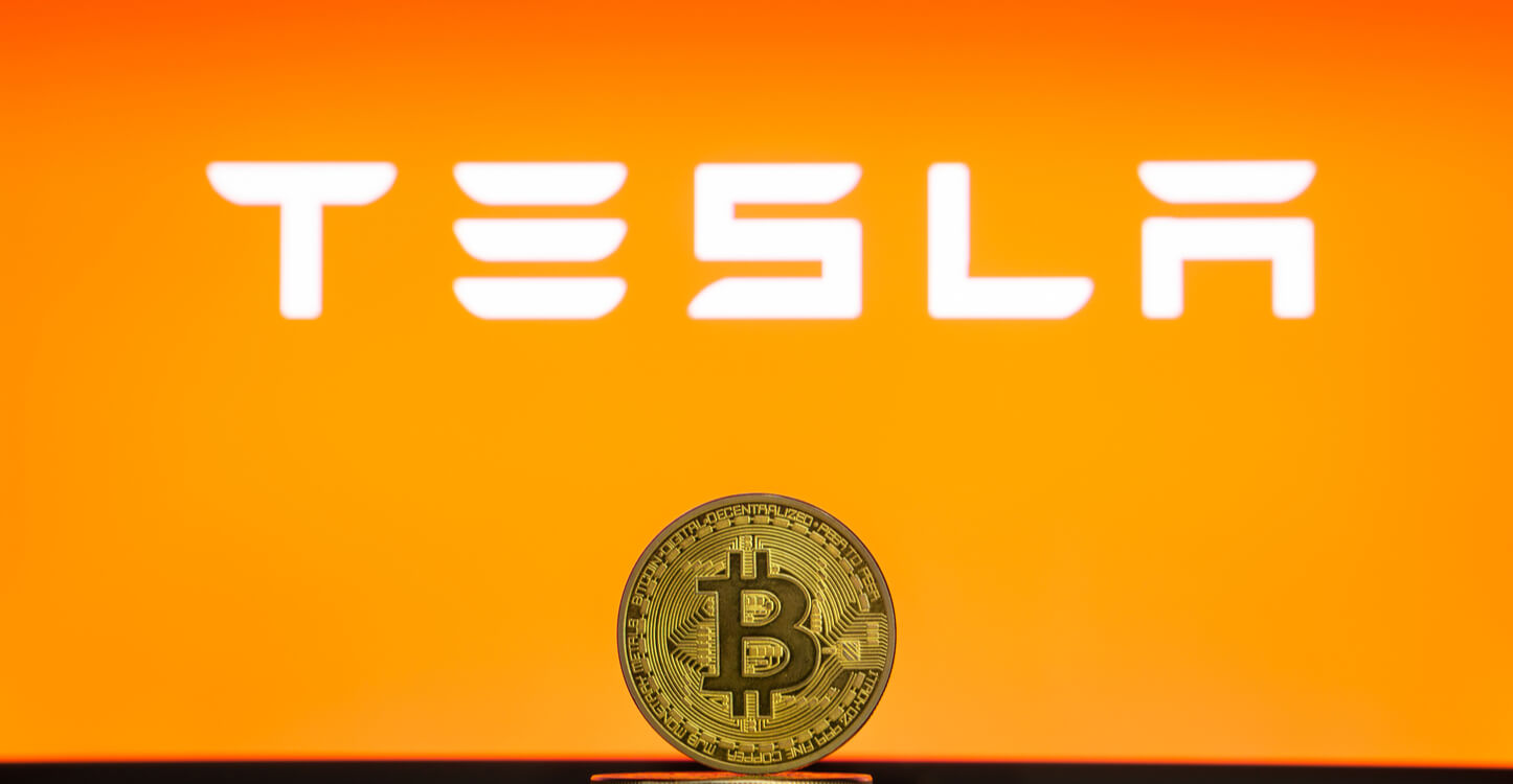 Bitcoin on a stack of coins with Tesla logo on a laptop screen