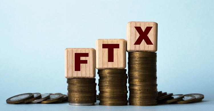 En bild av träkuber med texten FTX som vilar på staplar av mynt